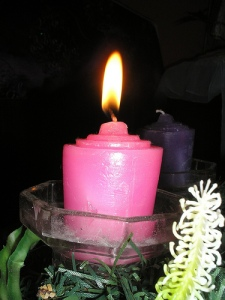 A lit pink advent candle