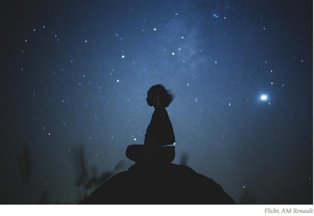 Woman contemplates under the stars