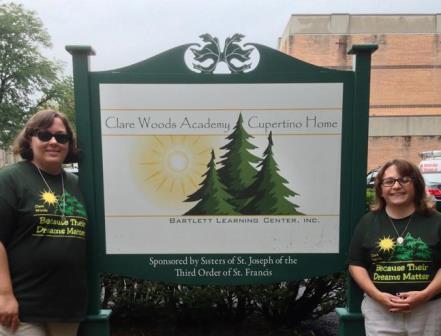 two-women-green-shirts-sign